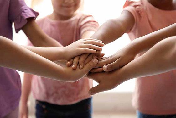 Kinder halten ihre Hände zusammen.