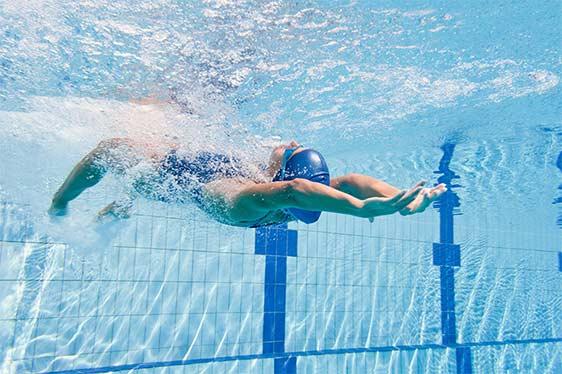 Schwimmerin unter Wasser in einem Hallenbad.